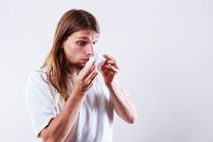 Man with hygienic tissue. Allergy and cold concept. Young long haired sick man with hygienic tissue. Guy blowing nose stock photo