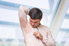 Man with hyperhidrosis sweating under armpit in office. Man with hyperhidrosis sweating under armpit in pink shirt Royalty Free Stock Photography