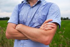 Man with hyperhidrosis sweating very badly under armpit in blue shirt,  on grey. Man with hyperhidrosis sweating very badly under armpit in blue shirt because of Royalty Free Stock Photography