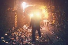 Man i övergiven tunnelbana fördärvad tunnel, ljus från slut eller utgång från den kusliga korridoren för tegelsten, industriell b Royaltyfria Foton