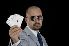Man i affärsdräkten som rymmer poker för 4 överdängare som spelar kort i hans hand Royaltyfri Fotografi
