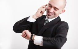 Man i affärsdräkten som ser på klockan, medan tala på mobiltelefonen royaltyfria bilder