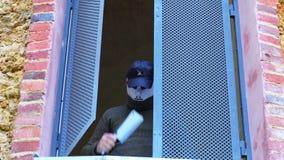 Man i allhelgonaaftonmaskering med kniven i huset på det öppna fönstret stock video