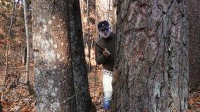 Man i allhelgonaaftonmaskeringen som döljer bak trädet lager videofilmer