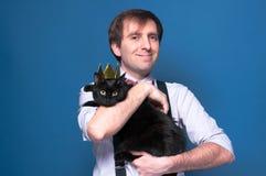 Man, i att le för skjorta som och för hängslen rymmer den svarta katten i den guld- kronan som står på blå bakgrund royaltyfria bilder