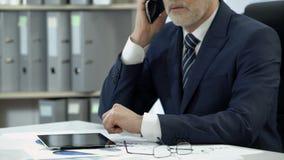 Man, i att ringa för affärsdräkt som talar på mobiltelefonen, minnestavlan och exponeringsglas på tabellen stock video