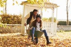 Man i Autumn Garden Gives Woman Ride i skottkärra royaltyfria foton