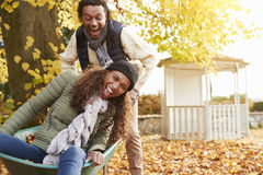 Man i Autumn Garden Gives Woman Ride i skottkärra royaltyfria bilder