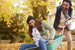 Man i Autumn Garden Gives Woman Ride i skottkärra arkivfoton