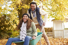Man i Autumn Garden Gives Woman Ride i skottkärra royaltyfri bild