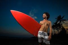 Man i baddräkten som rymmer en surfingbräda Fotografering för Bildbyråer