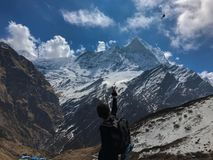Man i bergen som vinkar till förbigå för helikopter Nepal Annapurna strömkrets royaltyfri bild