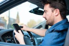 Man i bil genom att anv?nda mobiltelefonen p? hjulet royaltyfria foton