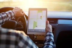 Man i bil- och innehavminnestavla med översiktsgps-navigering Royaltyfria Foton