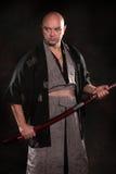 man i bilden av en samuraj med svärdet i hand Arkivbilder