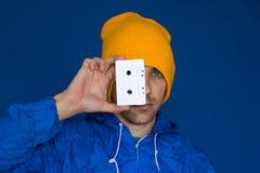 Man i blått omslag för tappning och gul hatt med ljudbandet arkivbilder