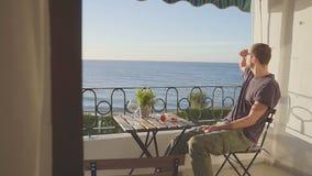 Man i blickar på havet från en balkong på Nerha spain arkivfilmer