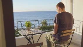 Man i blickar på havet från en balkong på Nerha spain stock video