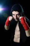 Man i boxninghoodieförkläde med huven på huvudet med slågna in handhandleder som är klara för att slåss Royaltyfria Bilder