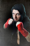 Man i boxninghoodieförkläde med huven på huvudet med slågna in handhandleder som är klara för att slåss Royaltyfri Foto