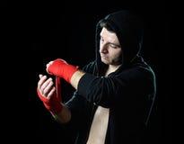 Man i boxninghoodieförkläde med huven på huvudet som slår in handhandleder för idrottshallutbildning Royaltyfri Foto
