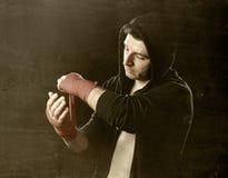 Man i boxninghoodieförkläde med huven på huvudet som slår in handhandleder för idrottshallutbildning Royaltyfria Foton