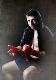 Man i boxninghoodieförkläde med huven på huvudet som slår in handhandleder för idrottshallutbildning Arkivbilder