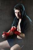 Man i boxninghoodieförkläde med huven på huvudet som slår in handhandleder för idrottshallutbildning Fotografering för Bildbyråer