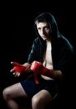 Man i boxninghoodieförkläde med huven på huvudet som slår in handhandleder för idrottshallutbildning Arkivbild