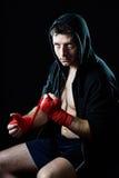 Man i boxninghoodieförkläde med huven på huvudet som slår in handhandleder för idrottshallutbildning Royaltyfri Bild