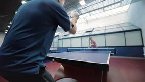 Man i den blåa T-tröja som spelar en bordtennis med kvinnan på domstolen stock video