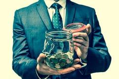 Man i den hållande pengarkruset för svart dräkt med mynt - retro stil Fotografering för Bildbyråer