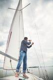 Man i den randiga skjortan som ser till och med kikare som seglar yachten Royaltyfri Foto