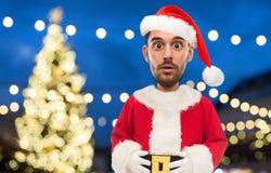 Man i den Santa Claus dräkten över julljus Royaltyfria Bilder