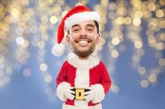 Man i den Santa Claus dräkten över julljus Arkivfoton