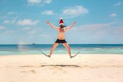 Man i den santa hatten på den tropiska stranden Arkivfoton