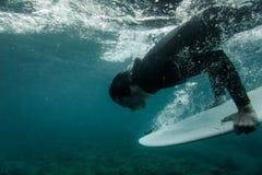 Man i den svarta baddräkten som rymmer en dyk för bränningbräde under vågen arkivfoton