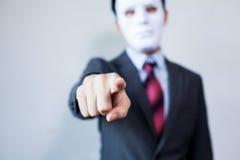 Man i den vita maskeringen i affärsdräkt som pekar fingrar på arkivbild