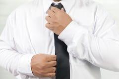 Man i den vita skjortan som av tar halsbandet Arkivbild