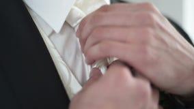 Man i den vita skjortan som binder ett band nära fönstret arkivfilmer