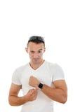 Man i den vita t-skjortan som pekar ett finger på klockan till kameran Arkivbild