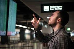 Man i det Front Of Arrivals And Departures brädet på flygplatsen för dublin för bilstadsbegrepp litet lopp översikt arkivbild