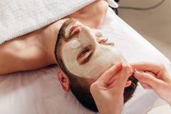 Man i det kosmetiska tillvägagångssättet för maskering i brunnsortsalong royaltyfria bilder