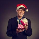 Man i det Santa Claus locket med gåvaasken royaltyfria foton