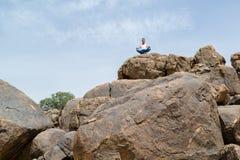 Man i djup yogakoncentration på ett stenigt berg - landskap fotografering för bildbyråer