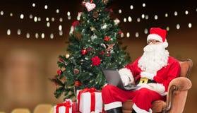 Man i dräkt av Santa Claus med bärbara datorn Royaltyfri Foto