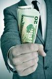 Man i dräkt med en bunt av amerikanska dollarräkningar Arkivbild