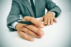 Man i dräkt med en penna i hans hand Royaltyfria Bilder