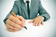 Man i dräkt med en penna i hans hand som är klar att skriva Royaltyfria Bilder