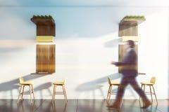 Man i dräkt som går i minimalistic kaféinre royaltyfri bild